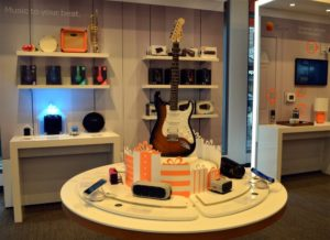 Guitar on a table surrounded by Bluetooth speakers.